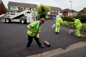 Workers re-surfacing a road in a residential area. Contractor Carillion Highway Maintenance working for Warwickshire County Council applying surface dressing of bitumen and stone chippings to the road... - John Harris - 2000s,2007,applying,contractor,contractors,Council,Council Services,Council Services,dressed,EBF Economy,gang,highway,LAB LBR Work,Local Authority,machine,machinery,machines,maintaining,maintenance,ma