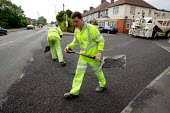 Workers re-surfacing a road in a residential area. Contractor Carillion Highway Maintenance working for Warwickshire County Council applying surface dressing of bitumen and stone chippings to the road... - John Harris - 07-06-2007
