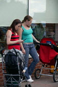 Young mothers with their pushchairs outside Tesco supermarket, retail park Birmingham - John Harris - 2000s,2007,adult,adults,arm,arms,Birmingham,bought,buy,buyer,buyers,buying,call,calls,CELLULAR,child,CHILDHOOD,children,cigarette,cigarettes,cities,city,commodities,commodity,communicating,communicati