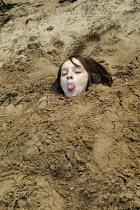 Small boy buried in sand on the beach, Staithes North Yorkshire. - John Harris - ,2000s,2007,beach,BEACHES,boy,boys,cheeky,child,CHILDHOOD,children,COAST,coastal,coasts,emilio,enjoying,enjoyment,fun,having,head,holiday,holiday maker,holiday makers,holidaymaker,holidaymakers,holida