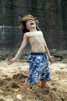 Small boy playing in sand on the beech, Staithes North Yorkshire. - John Harris - 2000s,2007,boy,boys,child,CHILDHOOD,children,COAST,coastal,coasts,emilio,enjoying,enjoyment,fun,having,holiday,holiday maker,holiday makers,holidaymaker,holidaymakers,holidays,juvenile,juveniles,kid,k