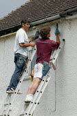 Workers fitting new guttering to a house. - John Harris - 2000s,2007,a,belt,Diaspora,drill,drilling,EARNINGS,EBF Economy,employee,employees,Employment,EQUALITY,fascia,fitter,fitters,fitting,fix,fixing,foreign,foreigner,foreigners,gutter,guttering,gutters,haz