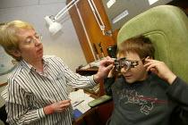 Consultant Optometrist testing the eyes of a child. - John Harris - 2000s,2007,boy,boys,child,CHILDHOOD,children,defects,emilio,examination,examinations,examining,eye,eyeglass,eyes,FEMALE,glasses,hea health,instrument,instruments,job,jobs,juvenile,juveniles,kid,kids,L