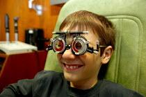 Consultant Optometrist testing the eyes of a child. - John Harris - 2000s,2007,boy,boys,child,CHILDHOOD,children,defects,emilio,examination,examinations,examining,eye,eyeglass,eyes,glasses,hea health,instrument,instruments,juvenile,juveniles,kid,kids,lens,lenses,male,