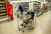 Elderly woman in a wheelchair with a basket shopping in Tesco with her daughter - John Harris - 02-12-2007