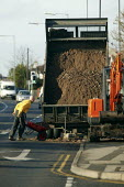 Building worker unloading loose load material from a tipup lorry to a wheelbarrow in constructing a new residential driveway. Warwickshire - John Harris - 09-01-2008