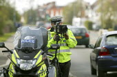 A Police officer monitoring traffic using a motorcycle based mobile speed camera as pupils walk past on their way home from school. Stratford upon Avon, Warwickshire. - John Harris - 03-04-2008