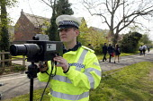 A Police officer monitoring traffic using a motorcycle based mobile speed camera as pupils walk past on their way home from school. Stratford upon Avon, Warwickshire. - John Harris - 20.20,2000s,2008,20-20,adult,adults,AUTO,AUTOMOBILE,AUTOMOBILES,AUTOMOTIVE,beam,beat,bike,bikes,camera,cameras,car,cars,child,CHILDHOOD,children,CLJ,device,Enforcement,equipment,force,gun,guns,highway