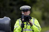 A Police officer monitoring traffic using a motorcycle based mobile speed camera, Stratford upon Avon, Warwickshire. - John Harris - 20.20,2000s,2008,20-20,adult,adults,AUTO,AUTOMOBILE,AUTOMOBILES,AUTOMOTIVE,beam,beat,bike,bikes,camera,cameras,car,cars,CLJ,device,Enforcement,equipment,force,gun,guns,highway,Infrared,laser,light,LTI