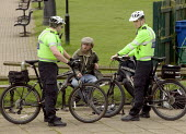 Police cyclists talking to homeless men in the park. - John Harris - 25-04-2008