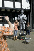 A living statue of William Shakespeare entertaining tourists outside the public library. Stratford upon avon - John Harris - 22-04-2008