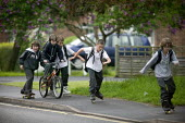 Pupils dashing along the street on roller skates on their way home from school. - John Harris - ,2000s,2008,adolescence,adolescent,adolescents,bicycle,bicycles,BICYCLING,Bicyclist,Bicyclists,BIKE,BIKES,boy,boys,child,CHILDHOOD,children,cycle,cycles,cycling,Cyclist,Cyclists,edu,educate,educating,