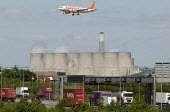 An Easyjet passenger jet come into land at East Midlands Airport over the M1 Motorway and Ratcliffe-on-Soar power station. - John Harris - 2000s,2008,aeroplane,aeroplanes,air,air transport,aircraft,airline,airplane,airplanes,airport,AIRPORTS,AUTO,AUTOMOBILE,AUTOMOBILES,AUTOMOTIVE,aviation,capitalism,capitalist,car,cars,chimney,chimneys,c