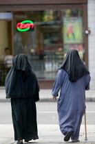 Women walking on the street. Hackney, London - John Harris - 2000s,2008,age,ageing population,BME Black minority ethnic,burka,burkas,burqa,burqas,cities,city,dress,elderly,FEMALE,Hackney,hajib,headscarf,hijab,islam,islamic,London,monotheistic,MUSLEM,muslim,musl
