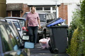 A man walks past rubbish recycling bins on the street outside a rented house of multiple occupancy. - John Harris - 08-08-2008