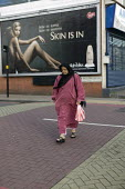 An elderly woman walking past an advertisement for a beauty product featuring a naked woman and the words skin is in. Sparkbrook, Birmingham. - John Harris - 2000s,2008,ace culture,advert,ADVERTISED,advertisement,advertisements,advertising,ADVERTISMENT,adverts,age,ageing population,asian,asians,BAME,BAMEs,beauty,bigotry,Black,BME,BME Black minority ethnic,