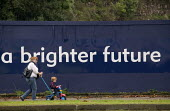 A mother and child passing a sign A Brighter Future, 750m regeneration plan for the old MG Rover car factory, Longbridge redevelopment site, Birmingham - John Harris - 2000s,2008,auto industry,Automotive,Birmingham,capitalism,capitalist,Car Industry,carindustry,child,CHILDHOOD,children,cities,city,close,CLOSED,closing,closure,closures,communicating,communication,Con
