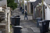 A man walking past a back alley. Merthyr Tydfil - John Harris - 2000s,2008,alley,alleyway,back,bin,bins,collection,council estate,Council Services,council estate,Council Services,dustbin,dustbins,eni,eni environmental issues,environment,Environmental Issues,EQUALI