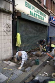 Construction workers working on a new pavement outside an employment agency called Employment Matters, Merthyr Tydfil - John Harris - 10-12-2008