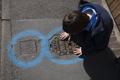 A child studying a water services inspection cover. Pavement markings showing the location of utilities underground prior to roadworks. Due to the huge number of utility services located within the ro... - John Harris - 08-05-2009