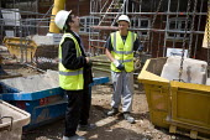 A Polish banksman assisting remote control crane to move materials. Building site, Warwickshire. - John Harris - 24-07-2009
