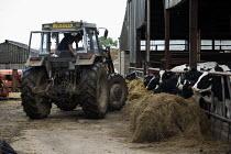A farmworker getting into his tractor in a farmyard in Warwickshire. - John Harris - 22-07-2009