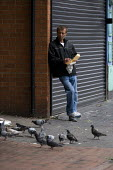 Man eating take away chips on the street and feral pigeons. Wednesbury town centre. - John Harris - 18-07-2009