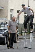 A painter and decorator using stilts to reach higher areas and to walk about the site. With his diabled customer. - John Harris - 06-09-2009