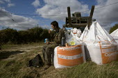 A farmworker takes a break at lunchtime to eat his packed lunch sitting on the Drilling or sowing Barley seeds on a farm in Rutland - John Harris - 2000s,2009,agricultural,agriculture,break,break time,capitalism,capitalist,cereal crop,crop,crops,DINNER,dinners,DINNERTIME,Drilling,EARNINGS,eat,eating,EBF,Economic,Economy,employee,employees,Employm