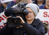 Women news camera operator filming a protest for the BBC. - John Harris - 06-12-2009