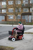 An elderly woman on a mobility scooter passes a derelict block of flats on a housing estate in Birmingham. - John Harris - 27-01-2010