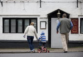 A family walks past a closed village Pub, Kineton, Warwickshire. - John Harris - 2010,2010s,adult,adults,Boarded Up,child,CHILDHOOD,children,closed,closing,closure,closures,couple,COUPLES,DAD,DADDIES,DADDY,DADS,daughter,DAUGHTERS,derelict,DERELICTION,disused,EARLY YEARS,EBF,Econom
