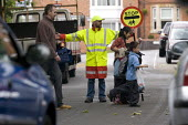 A school crossing patrol warden helping pedestrians to cross the road in safety. - John Harris - 17-07-2010