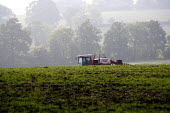 A landworker driving a sprayer, making a pre-emergent pesticide application onto a wheat crop, Warwickshire. - John Harris - 2010,2010s,agricultural,agriculture,agrochemicals,application,capitalism,capitalist,chemical,chemicals,crop,crops,driver,drivers,driving,EBF,Economic,Economy,employee,employees,Employment,eni,environm