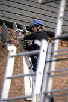 An engineer installing a Sky TV satellite dish onto a house on a housing estate - John Harris - 27-10-2010