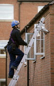 An engineer installing a Sky TV satellite dish onto a house on a housing estate - John Harris - 27-10-2010