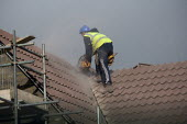 A worker cutting tiles on a roof. New homes being built on an estate, West Wick, Weston-super-Mare - John Harris - 10-11-2010