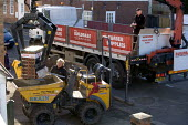 Building workers taking delivery of bricks for a house extension from Builder Merchants Buildbase materials supplier. Unloading the materials using a crane from a lorry - John Harris - 2010,2010s,brick,bricks,builder,builders,Building,Building Worker,BUILDINGS,Construction Workers,crane,CRANES,DELIVERING,delivery,driver,drivers,driving,EBF,Economic,Economy,employee,employees,Employm