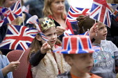 A little princess. Children at a Street Party watching the Royal Wedding Day on TV and waving union jack flags, Stratford upon Avon, Warwickshire - John Harris - 29-04-2011