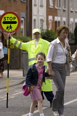 School crossing patrol officer with a Lollypop, helping parents and pupils to cross the road safely, Ipswich - John Harris - 2010,2010s,child,CHILDHOOD,children,cross,crosses,crossing,EARNINGS,employee,employees,Employment,EQUALITY,FEMALE,helping,highway,Income,INCOMES,inequality,job,jobs,juvenile,juveniles,kid,kids,LAB,LBR