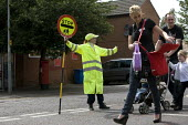 Lollypop operatives helping parents collecting their children to cross the road outside a Junior and infants School, Ipswich, Suffork. - John Harris - 2010s,2011,adult,adults,age,ageing population,child,CHILDHOOD,children,cities,city,collecting,Council Services,Council Services,Council Workers,cross,Crossing The Road,EARNINGS,edu,educate,educating,e