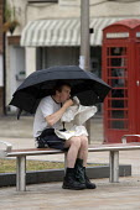 A lone tourist eating chips in the rain, Stratford on Avon, Warwickshire. - John Harris - 04-08-2011