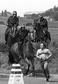 Riot police on horseback chase lone, bare-chested, striking miner at the Battle of Orgreave - a violent confrontation between police and picketing miners at the coking plant in South Yorkshire. The pi... - John Harris - ,1980s,1984,adult,adults,animal,animal animals,animals,baton batons,Battle of Orgreave,BSC,CLJ,coke works,coking plant,confront,confrontation,confronted,confronting,DISPUTE,DISPUTES,domesticated ungul
