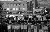 Ranked lines of police officers and riot police prevent striking miners from approaching the Orgreave coking plant during the miners' strike. - John Harris - 28-05-1984