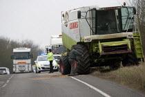 Sweeping up grain after an road traffic accident invloving a Combine Harvestor, Warwickshire. - John Harris - 09-03-2013