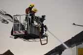 Firefighters spraying a jet of water from a hydraulic platform. Fire and Rescue Service attending a fire, Birmingham - John Harris - 2010s,2013,adult,adults,Birmingham,building,buildings,Burnt Out,cities,city,collapsed,DIA,Emergency Services,employee,employees,Employment,fire,Fire AND Rescue,fire brigade,Fire Engine,firefighter,fir