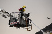 Firefighters spraying a jet of water from a hydraulic platform. Fire and Rescue Service attending a fire, Birmingham - John Harris - 27-03-2013