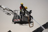 Firefighters spraying a jet of water from a hydraulic platform. Fire and Rescue Service attending a fire, Birmingham - John Harris - ,2010s,2013,adult,adults,Birmingham,building,buildings,Burnt Out,cities,city,collapsed,DIA,Emergency Services,employee,employees,Employment,fire,Fire AND Rescue,fire brigade,Fire Engine,firefighter,fi