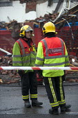 Red and white striped tape used to cordon off an area during an incident to protect the public. Sector Commanders in discussion. Fire and Rescue Service attending a fire, Birmingham - John Harris - 2010s,2013,adult,adults,Birmingham,cities,city,command,commander,communicating,communication,conversation,conversations,cordon,DIA,dialogue,discourse,discuss,discusses,discussing,discussion,Emergency