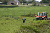 A farmworker unfolding the spraying rig, crop spraying using a tractor on a farm in Oxfordshire - John Harris - 21-05-2012